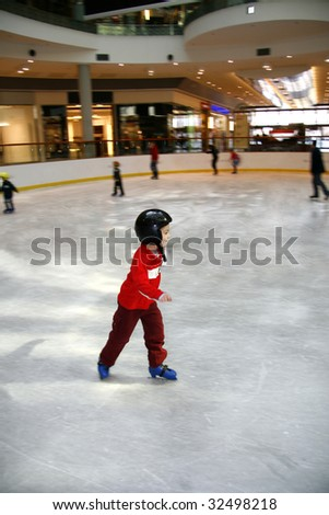 Winter time. Young boy learning to skate - stock photo