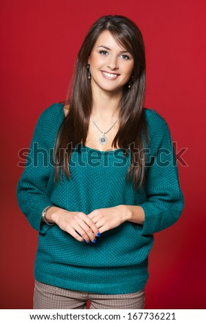 Winter time. Young smiling brunette woman in warm clothes standing casually