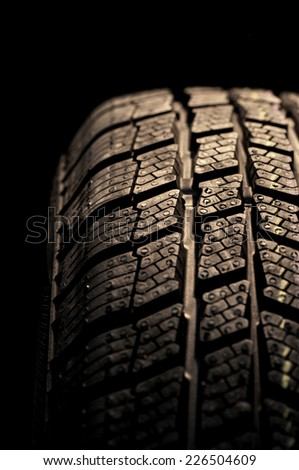 Winter tire isolated on black background - stock photo