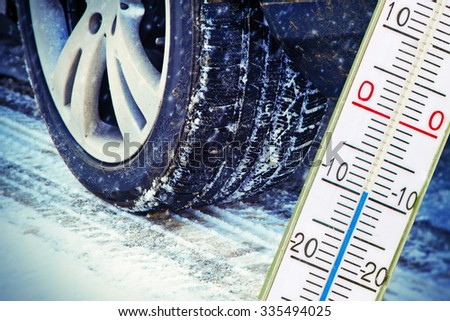 Winter tire with thermometer - stock photo