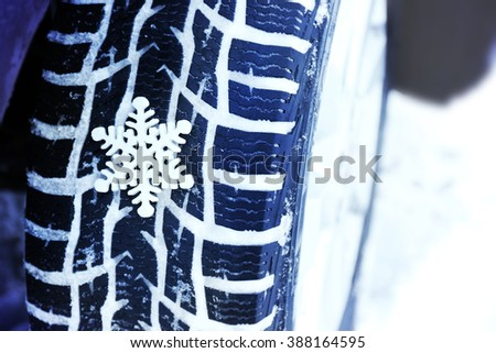 Winter tires in snow with snowflake, closeup - stock photo