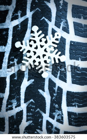 Winter tires in snow with snowflake, macro view - stock photo