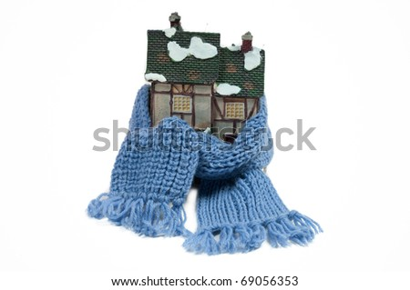 Winter toy half-timbered house wrapped in a shawl isolated on white background - stock photo
