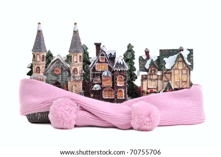 Winter toy half-timbered houses wrapped in pink scarf isolated on white background - conceptual view of protecting or isolating house - stock photo