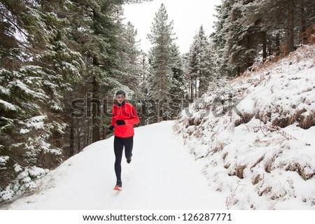 Winter trail running: man takes a run on a snowy mountain path in a pine woods. - stock photo