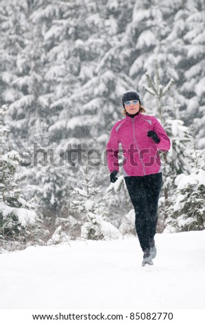 Winter training - Woman running in winter forest - stock photo