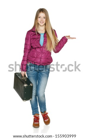 Winter traveler. Smiling young female in winter coat in full length standing with the old fashioned suitcase holding blank copy space on her open palm , isolated on white background - stock photo