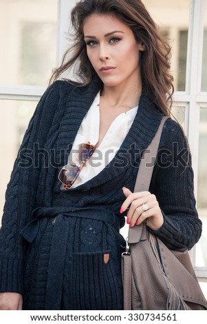 winter trendy fashion young woman in dark blue cardigan and  white shirt  stand in front glass doors outdoors - stock photo