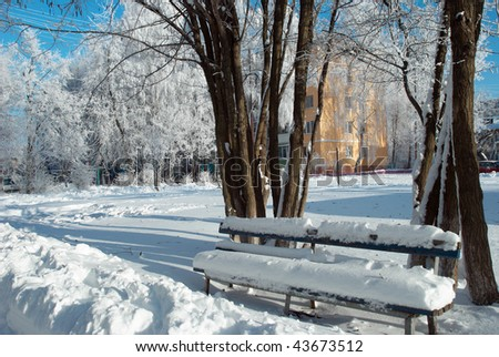 Winter urban landscape. Snow covered bench near the trees. - stock photo