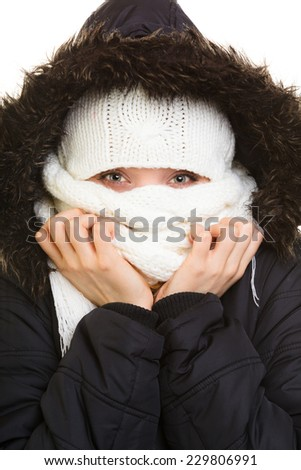 Winter vacation. Girl in warm clothes. Young woman covering her face with scarf hood from cold isolated on white.