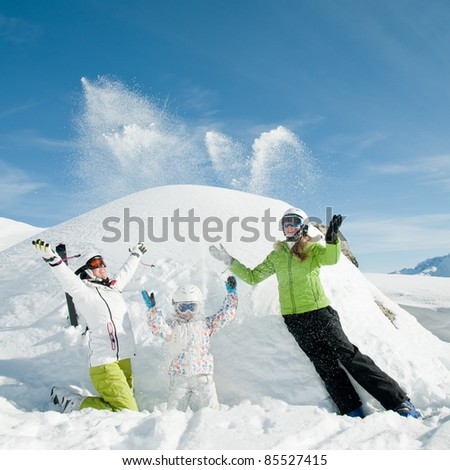 Winter vacation - happy skiers playing in snow (copy space)