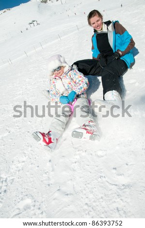 Winter vacation - young skiers resting on ski slope (space for text) - stock photo