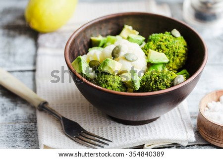 Winter vegetable salad with broccoli, cauliflower, avocados, pumpkin seeds, lemon and spices, healthy dinner - stock photo