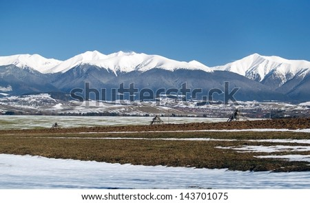 Winter view of fields near Liptovsky Mikulas and snow covered peaks of Rohace mountains in the distance. Rohace are part of the Western Tatras in the Slovakia.