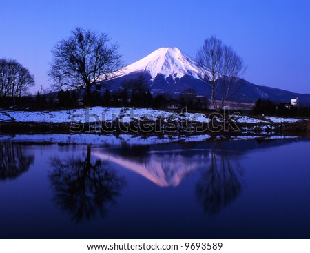 Winter view of Mount Fuji with mist and reflections in a lake - stock photo