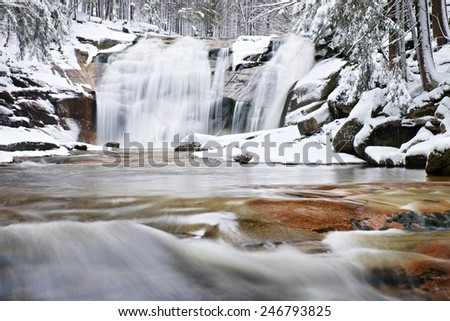 Winter view over snowy boulders to cascade of waterfall. Wavy water level.. Stream in deep freeze. - stock photo