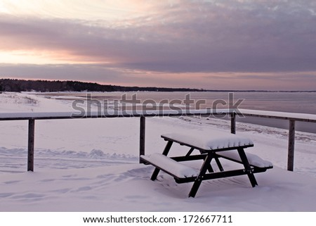 Winter view to the beach with a bench full of snow