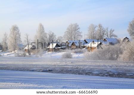 winter village on coast river - stock photo