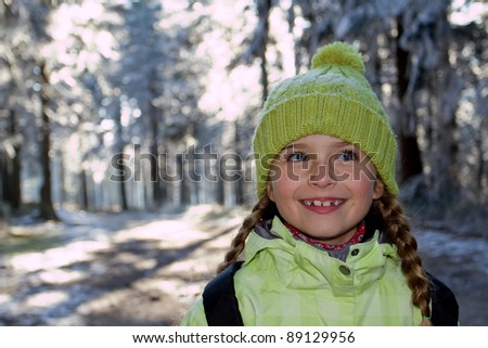 Winter walking - portrait of little girl in winter forest - stock photo