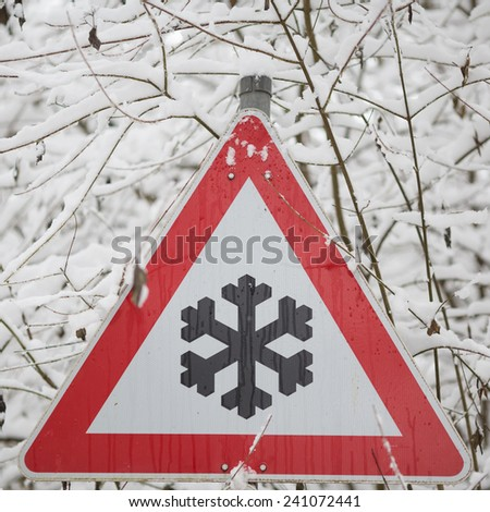 winter warning sign shows danger of ice and snow at street  - stock photo