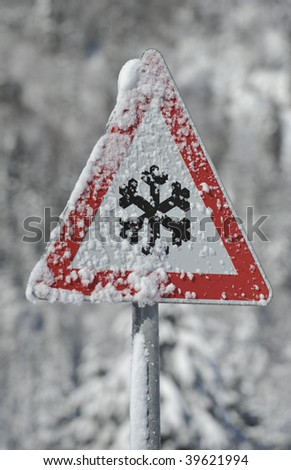 winter warning sign shows danger of ice and snow at street, highway or road - stock photo
