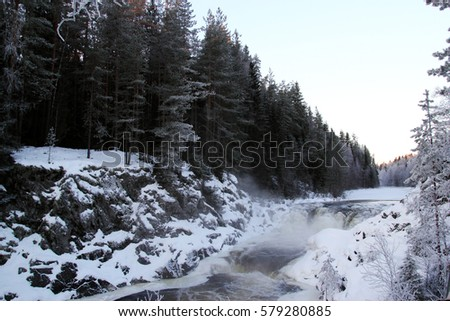 Winter waterfall Kivach in Karelia Russia, winter forest and river