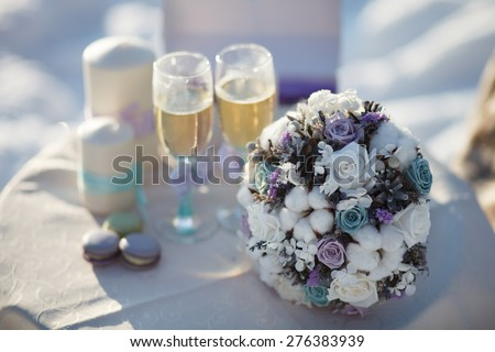 Winter wedding bouquet. Wedding bouquet of flowers lying on a chair near two wedding glasses and candle. - stock photo