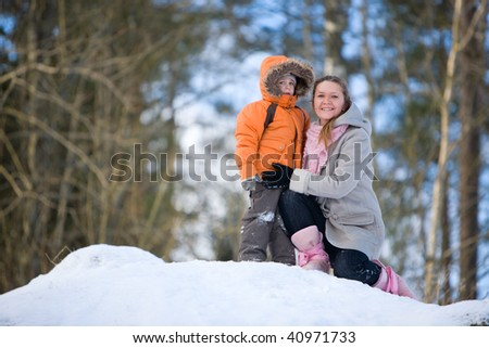 Winter weekend. Mother and son on beautiful winter day outdoors.