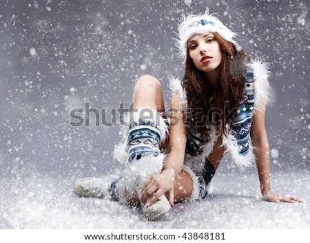 Winter wild woman on snow and grey background - stock photo