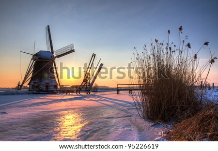 winter windmill at sunset between Abcoude and Baambrugge in the Netherlands, near Amsterdam - stock photo