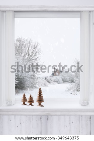 Winter window with turned wooden Christmas trees sitting on the ledge - stock photo