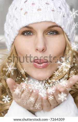 winter woman blowing a gift os snow to the camera - stock photo