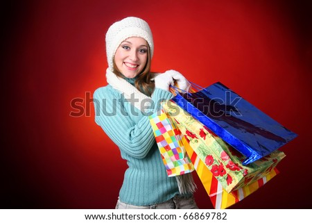 Winter woman carrying colorful shopping bags - stock photo