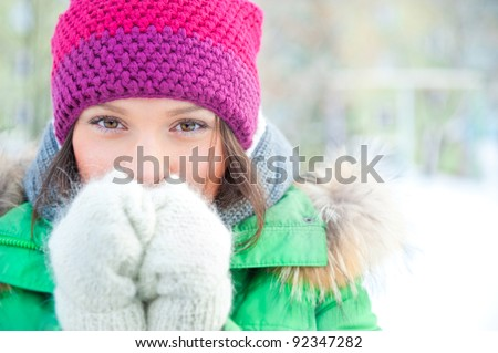Winter woman in snow looking at camera outside on snowing cold winter day. Portrait Caucasian female model outside in first snow - stock photo