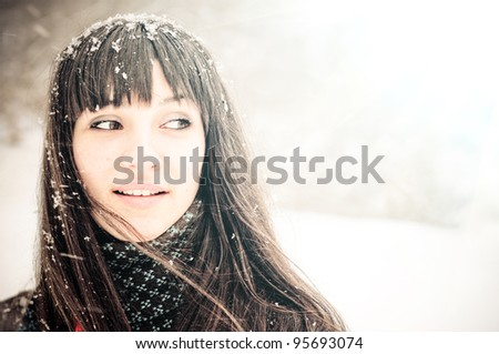 winter woman in snow looking at copy space outside on snowing cold winter day. - stock photo