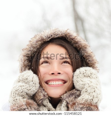Winter woman looking up happy and smiling outdoors in snow on cold winter day. Asian girl model in her twenties. - stock photo