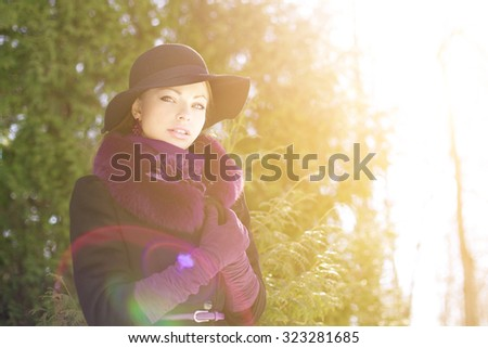 Winter woman on background of winter landscape, sun. Fashion girl in forest wonderland. Winter sunset scene. Model in sunlight, backlight - stock photo