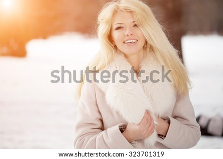 Winter woman on background of winter landscape sun. Fashion girl in forest wonderland. Winter sunset scene. Model in sunlight, backlight - stock photo