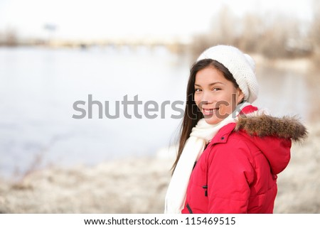 Winter woman portrait outside. Mixed-race girl smiling happy in cold winter landscape wearing winter clothing smiling happy looking at camera. Asian Chinese and Caucasian ethnicity. Quebec, Canada. - stock photo