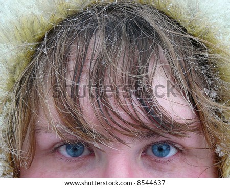 winter, woman's blue eyes and hair under snow - stock photo