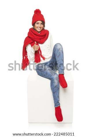 Winter woman wearing knitted warm red scarf, hat and socks sitting on blank billboard placard sign and gesturing thumb up - stock photo