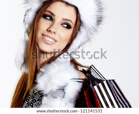 Winter woman with shopping bags over white - stock photo