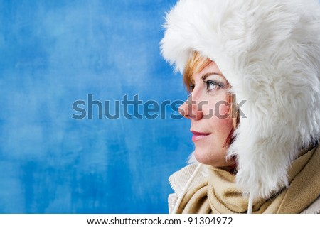 Winter woman with white fur hat in side profile. Studio shot with copy space against a blue background. - stock photo