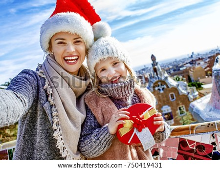Winter wonderland in Barcelona at Christmas. happy trendy mother and daughter travellers with a little Christmas tree and present box at Guell Park in Barcelona, Spain taking selfie