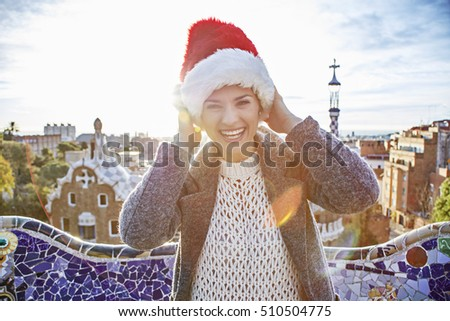 Winter wonderland in Barcelona at Christmas. Portrait of cheerful trendy traveller woman in a Santa hat at Guell Park in Barcelona, Spain having fun time