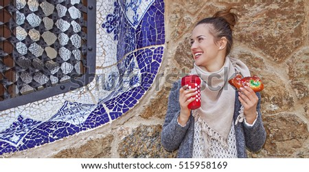 Winter wonderland in Barcelona at Christmas. Portrait of happy traveller woman with a cup of hot beverage and a piece of traditional king cake at Guell Park in Barcelona, Spain looking aside