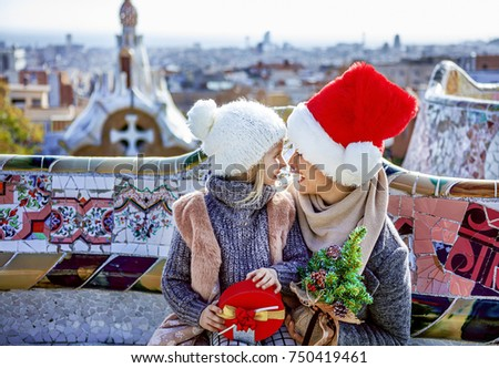 Winter wonderland in Barcelona at Christmas. Portrait of smiling trendy mother and daughter tourists with little Christmas tree and present box at Guell Park in Barcelona, Spain looking at each other