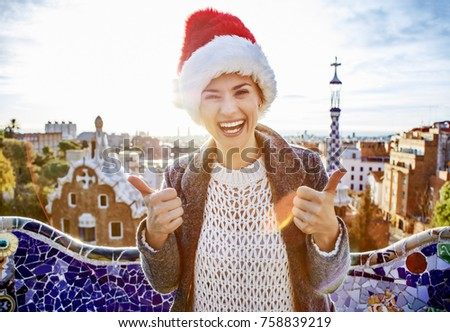 Winter wonderland in Barcelona at Christmas. Portrait of smiling young tourist woman in a Santa hat at Guell Park in Barcelona, Spain showing thumbs up