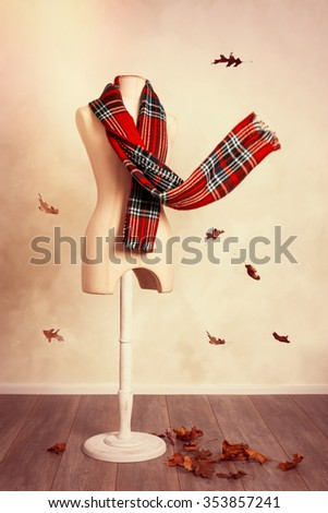 Winter wool tartan scarf with falling leaves - stock photo