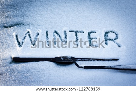 Winter written in snow on car windscreen below windscreen wiper - stock photo